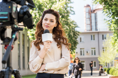 attractive serious news reporter with microphone looking at digital video camera Stock Photo