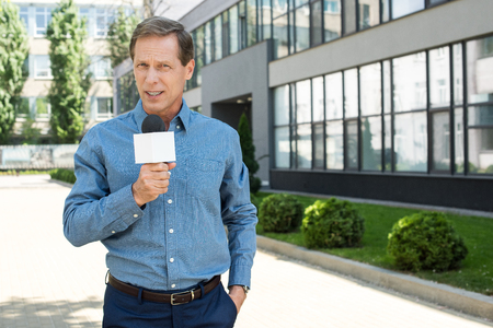 professional mature news reporter talking with microphone