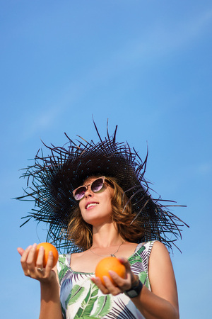 bottom view of attractive young woman in hat holding oranges against blue sky Stockfoto