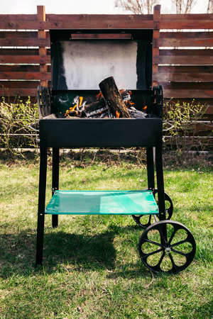 Metal outdoor grill with logs burning on fire Stock Photo