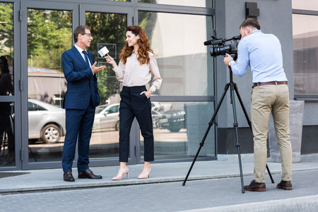 professional cameraman and news reporter interviewing businessman near office building