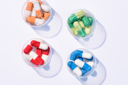 top view of various colorful pills in plastic cans on white