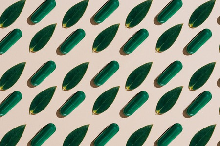 top view of phytotherapy capsules with green leaves in rows pattern on beige tabletop Banco de Imagens