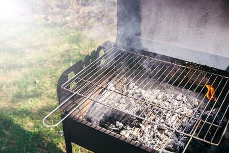 Grill with burning coals ready for barbecue outdoors Stock Photo