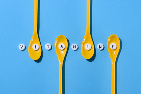 top view of yellow plastic spoons and pills with vitamine lettering in row on blue Stock Photo