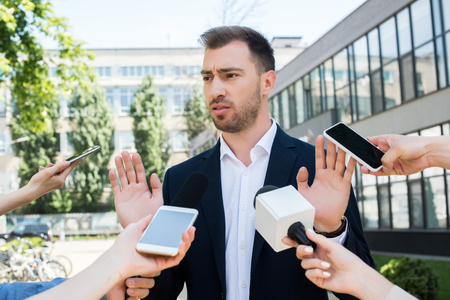 journalists interviewing serious businessman with microphones and smartphones Stock Photo