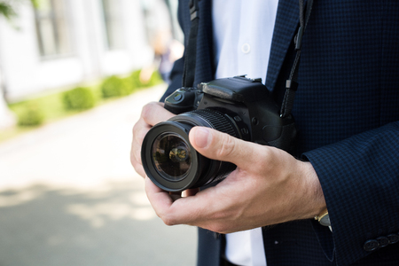 partial view of photojournalist in formal wear holding photo camera