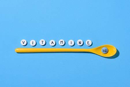 top view of yellow plastic spoon and pills with vitamine b12 lettering on blue