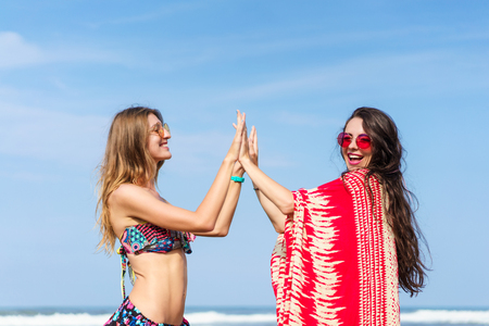 beautiful young women giving high fives on beach