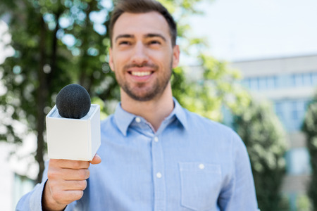 smiling anchorman taking interview with microphone