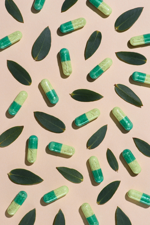 top view of phytotherapy pills with green leaves pattern on beige surface Banco de Imagens