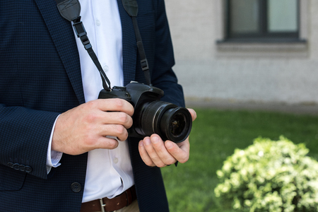 partial view of photojournalist in suit with digital photo camera Stock Photo