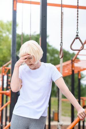 senior tired sportswoman standing on sports ground