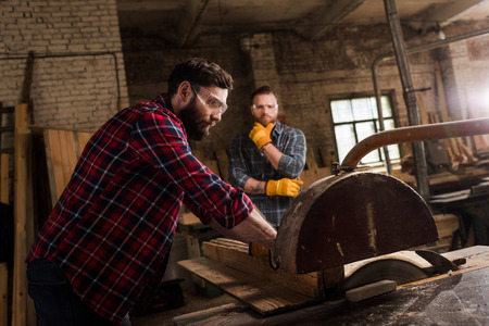 carpenter in safety googles using machine saw and partner standing behind at sawmill Stock Photo