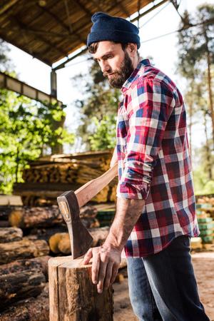 bearded lumberjack in checkered shirt preparing to chop log at sawmill