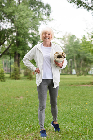 smiling senior woman standing with yoga mat in green park Stock Photo