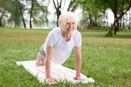 smiling elderly woman doing plank on yoga mat on lawn 스톡 콘텐츠