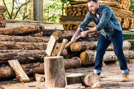 lumberjack in checkered shirt chopping log at sawmill