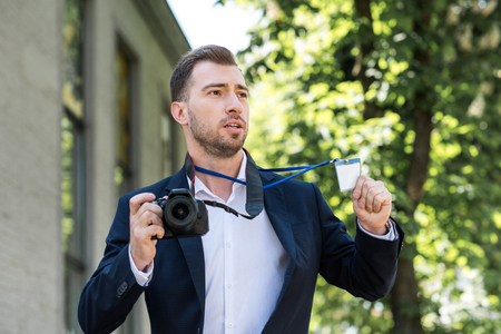 photojournalist in formal wear with digital photo camera and press pass
