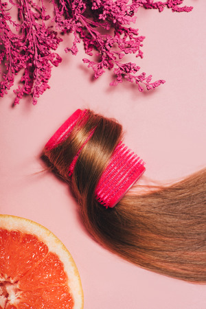top view of hair rolled over curler with flowers and orange on pink surface Фото со стока - 106605319