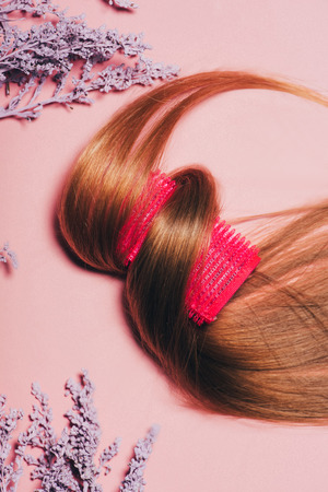 top view of hair rolled over curler with flowers on pink surface 스톡 콘텐츠 - 106605320