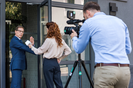 professional cameraman and female journalist with businessman refusing interview
