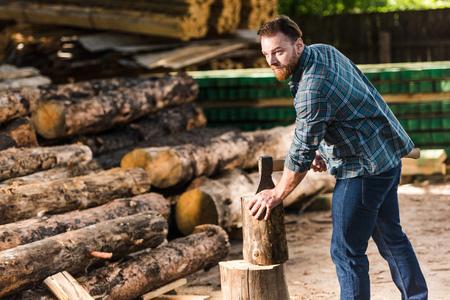 bearded lumberjack in checkered shirt chopping log at sawmill