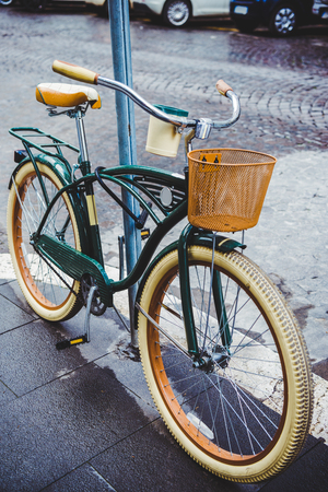 vintage bicycle with basket parked on street of Rome, Italy
