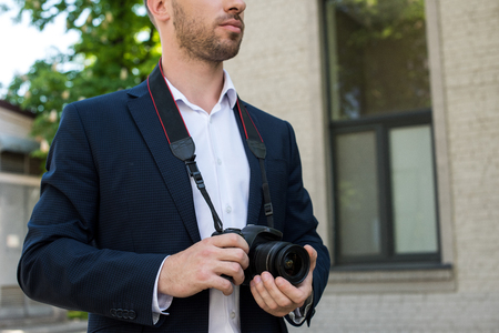 cropped view of photojournalist in formal wear with digital photo camera