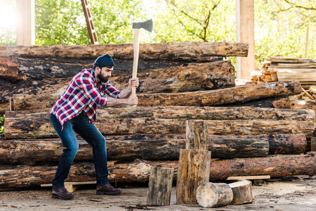 side view of bearded lumberjack in checkered shirt chopping log at sawmill Zdjęcie Seryjne