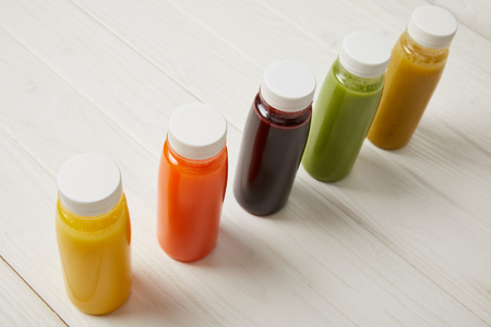detox smoothies in bottles standing in row on white wooden background