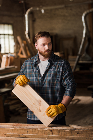 carpenter in protective gloves working with wooden plank at sawmill