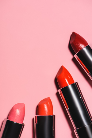 top view of various lipsticks of red shades on pink surface Standard-Bild - 106606443