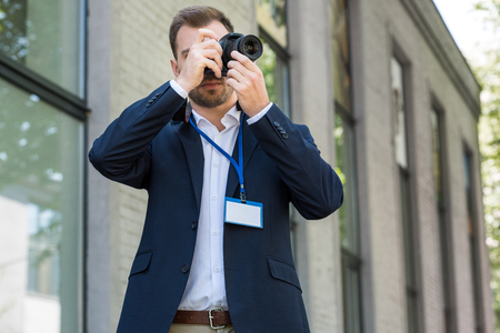 photojournalist in formal wear with press pass taking photo Stock Photo