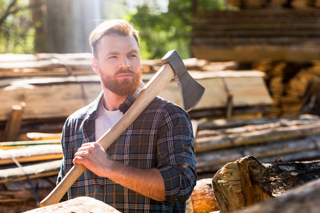 lumberjack in checkered shirt holding axe on shoulder at sawmill Zdjęcie Seryjne