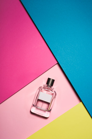 top view of glass bottle of perfume on colorful surface Banco de Imagens
