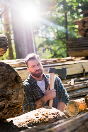 lumberjack in checkered shirt with tattooed hand holding axe at sawmill Zdjęcie Seryjne