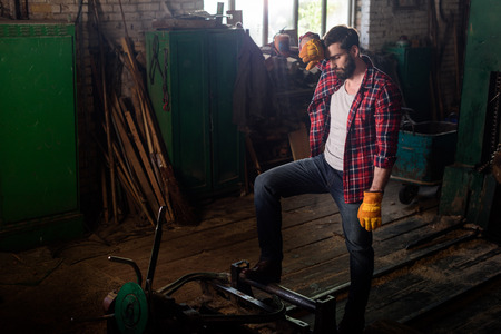 tired worker wiping forehead and standing near machine at sawmill