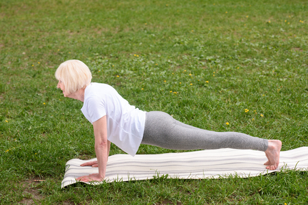 elderly woman doing plank on yoga mat on lawn Stock Photo