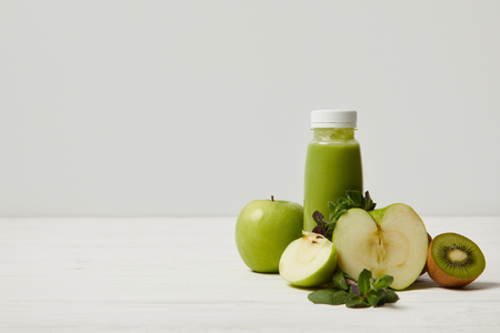 Batido de desintoxicación verde con manzanas, kiwi y menta y sobre superficie de madera blanca