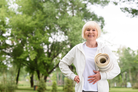 cheerful elderly woman holding yoga mat in park