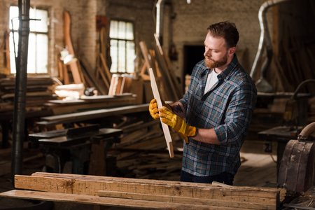 bearded carpenter in protective gloves working with wood at sawmill Zdjęcie Seryjne