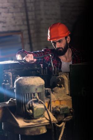 worker in protective helmet repairing machine tool at sawmill Zdjęcie Seryjne