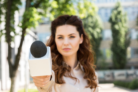 serious female journalist taking interview with microphone Stock Photo