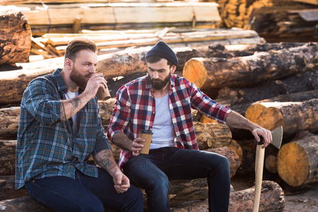 two bearded loggers sitting with disposable cups of coffee and axe Stockfoto