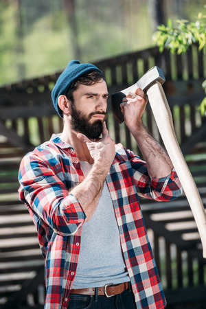 lumberjack in checkered shirt shaving beard by axe at sawmill