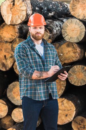 bearded lumberjack in protective helmet writing in clipboard on logs background Zdjęcie Seryjne