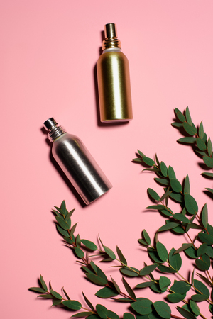 top view of metal bottles of perfumes with green branches on pink surface Banco de Imagens