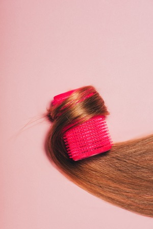 top view of hair rolled over curler on pink surface Фото со стока - 106608192