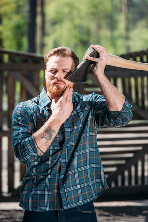 bearded lumberjack with tattooed hand shaving by axe at sawmill